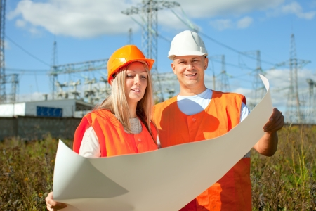 Portrait of two builders works at electric power plant photo