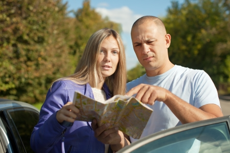 Traveler couple looking at the map on the country road photo