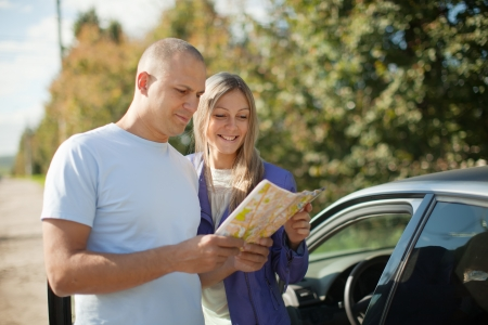 road map: tourist couple looking at the map on the road. Focus on woman Stock Photo