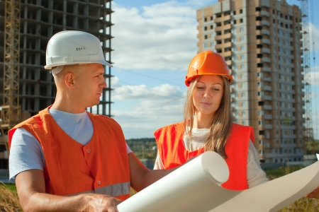 Portrait of two builders standing at building site  photo