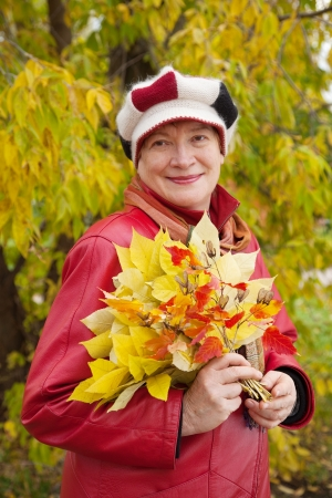Happy mature woman  in coat outdoors in autumn Stock Photo - 15296895