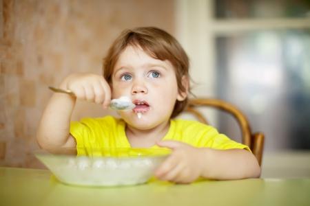 2 anni Bambino si mangia con il cucchiaio di latte Archivio Fotografico