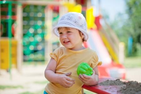 the sandbox: two-year child playing  in sandbox