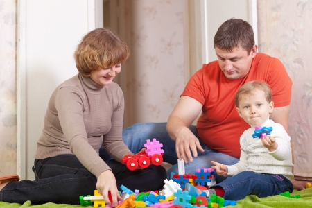 Happy parents and child plays with meccano set in home Stock Photo - 15256083