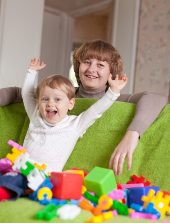 Happy mother plays with child in home interior  photo