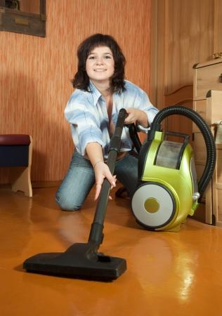 Sexy girl cleans with vacuum cleaner at home photo