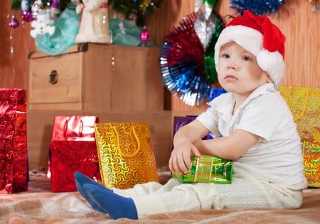 クリスマス プレゼント自宅で小さな男の子が座っています。