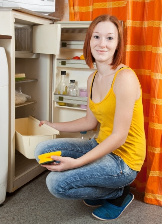 20 25: Young woman  defrosting the refrigerator at her kitchen