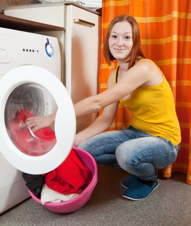 Woman loading the washing machine at her home photo