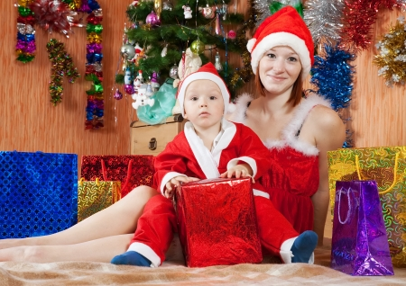2 to 3 years: Ragazzo vestito come Babbo Natale con la madre di celebrare il Natale in salotto