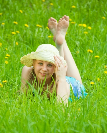 girl in hat lying in meadow grass photo