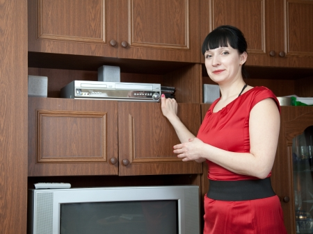 Woman using compact-disk player with TV in home photo