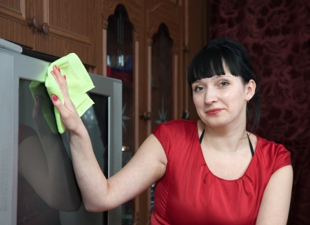 mujer limpia la televisi�n en casa Foto de archivo - 15256148