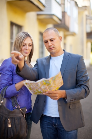 tourist couple looking at the map in the city photo