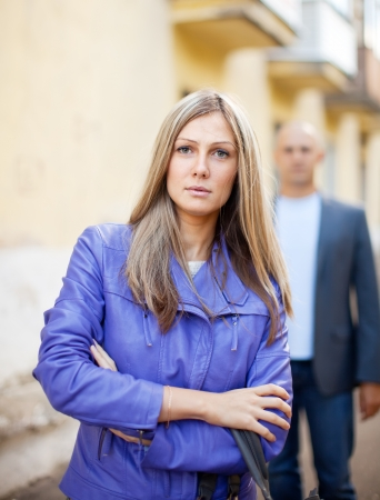 lovers quarrel: Man walks behind woman on the city street Stock Photo