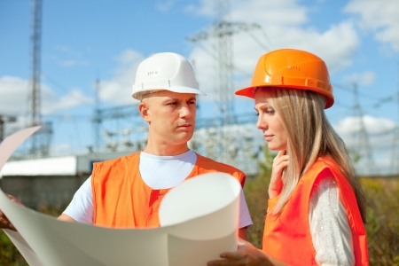 two workers wearing protective helmet works at electrical power station. Focus on man photo
