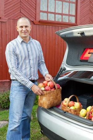 Guy puts apples harvest in the trunk of car photo