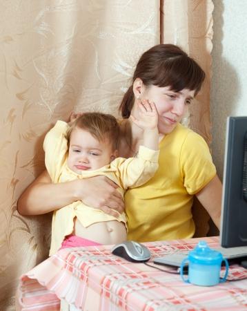 madre trabajadora: Mujer con beb� llorando trabajando con el ordenador en casa Foto de archivo