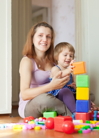 Happy pregnant mother plays with child in home interior photo