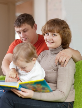 parents with child looks the book in home interior Stock Photo - 15360832