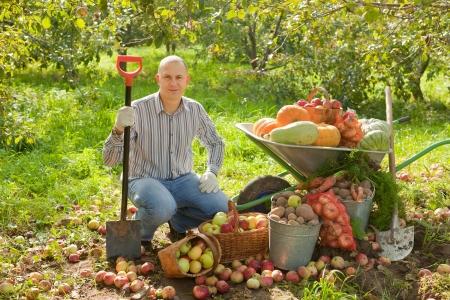squash vegetable: Happy man with vegetables harvest in garden