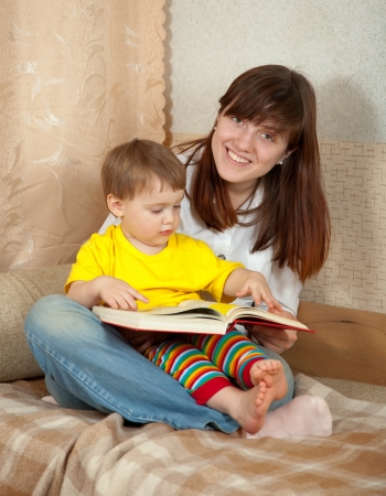 Mother and daughter reading  book together on couch in home Stock Photo - 15390923