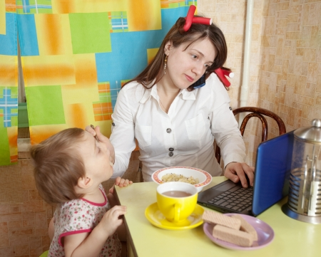 bustle: Mother feeding baby and  using  latop at kitchen in morning Stock Photo
