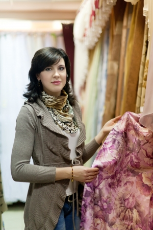 woman  chooses draperies at shop photo