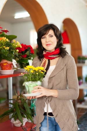 woman in the shop surrounded by different flowers photo