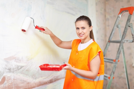 housepainter: Female housepainter paints wall with roller