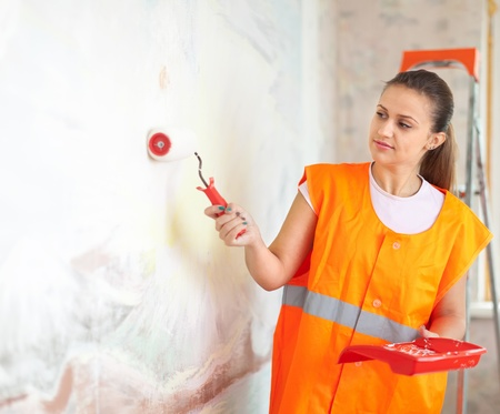 Female house painter paints wall with roller Stock Photo - 15401960