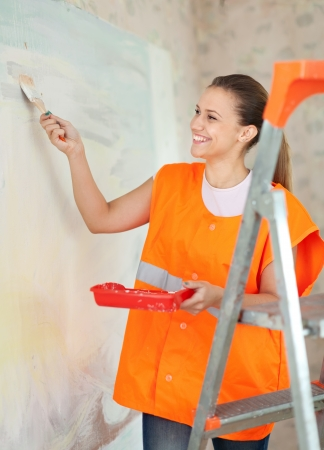 priming brush: Female house painter paints wall with a brush Stock Photo