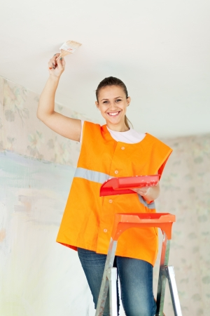 priming brush: Female house painter paints the ceiling with a brush Stock Photo