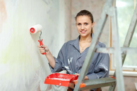 Happy woman paints wall with roller at home Stock Photo - 15401965