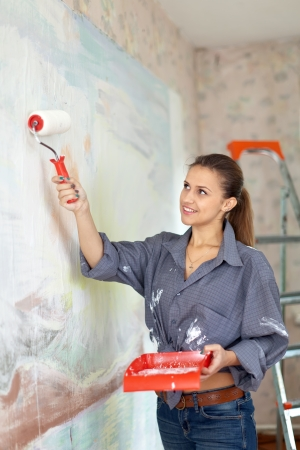 Happy girl paints wall with roller photo