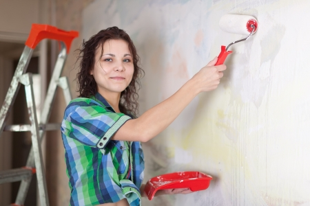 woman paints wall with roller at home Stock Photo - 15443003