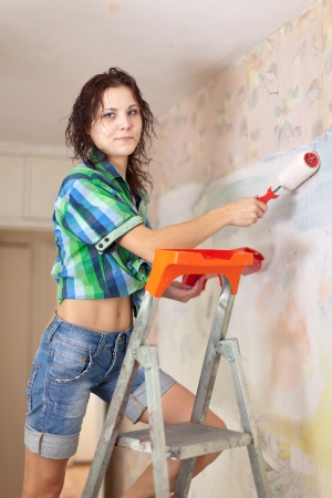Young woman makes repairs in the apartment  photo