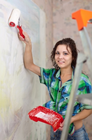 Happy girl paints wall with roller at home photo