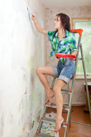 spalpeen:  girl paints wall with brush at home