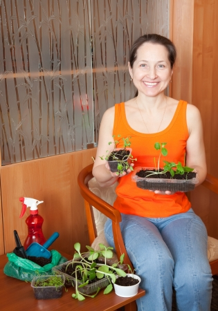 Female gardener with various sprouts at home photo