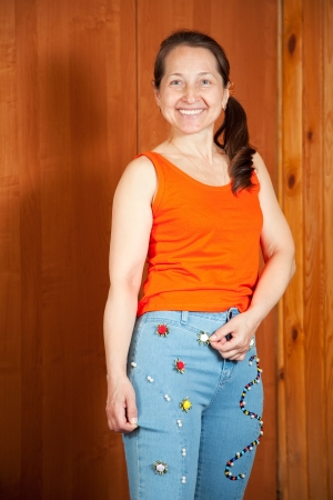 Mature woman  shows a handmade jeans beaded by herself Stock Photo - 15470467