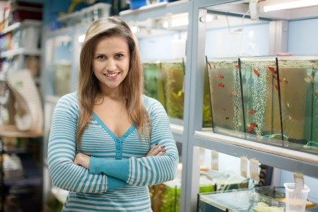 petshop: Woman near aquariums with fishes in pet-shop Stock Photo