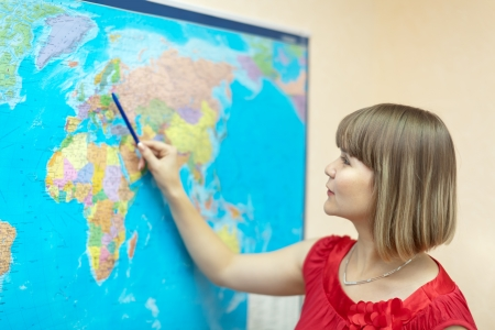 eastward: Woman showing something on the world map at house
