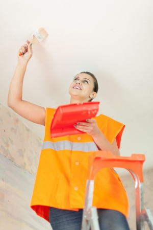 spalpeen: Female house painter paints the ceiling with a brush Stock Photo
