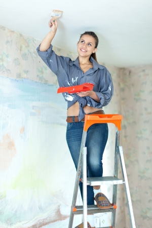 Woman paints ceiling with brush at home Stock Photo - 15470510