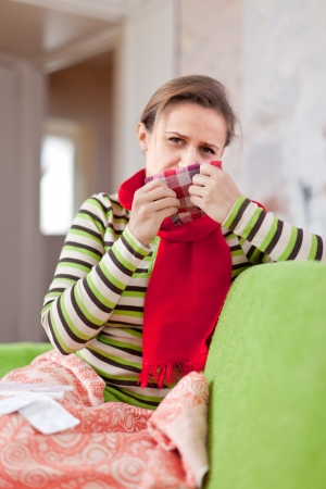 sick woman uses handkerchief in home Stock Photo