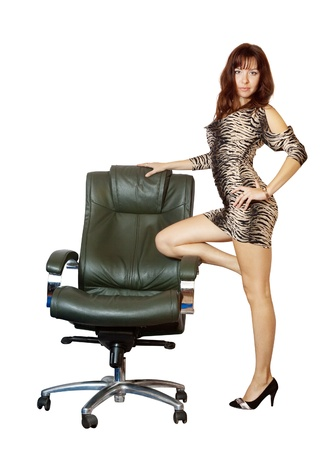 Sexy woman standing with luxury office armchair, isolated over white background photo
