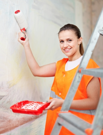 Female house painter paints wall with roller photo