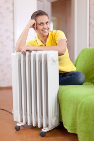 heat register:  smiling woman  near warm radiator  in home Stock Photo