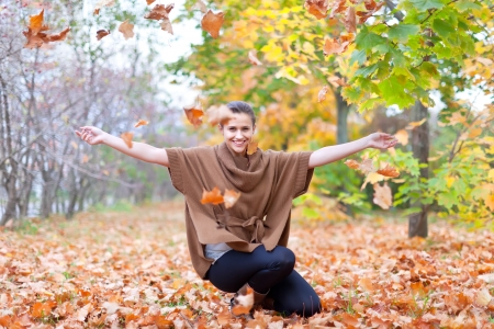 Woman throws autumn leaves in the park photo